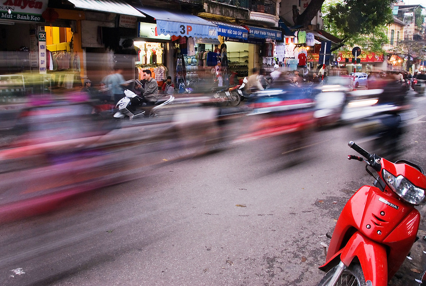 Motorbikes speed by on a busy street in the Old Quarter of Hanoi, Vietnam.