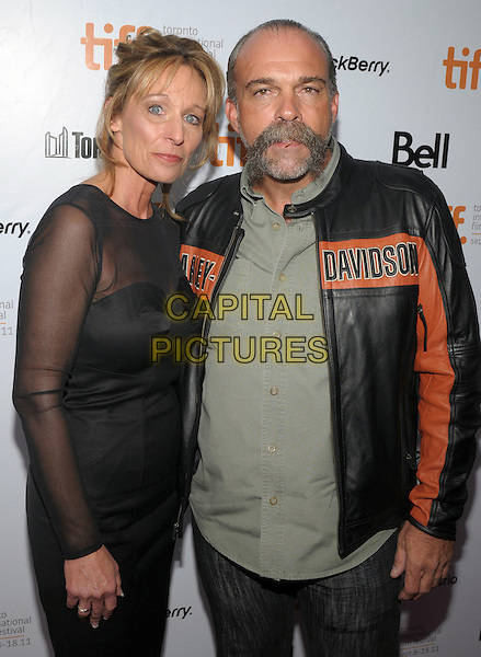 "guest & Sam Childers.""Machine Gun Preacher"" Premiere - 2011 Toronto International Film Festival held at Roy Thomson Hall, Toronto, Ontario, Canada..September 11th, 2011.half length black dress sheer leather jacket orange green top moustahce mustache facial hair  .CAP/ADM/BPC.©Brent Perniac/AdMedia/Capital Pictures."