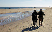 Nederland Texel 2015. Oudere man en vrouw wandelen op het strand in De Koog