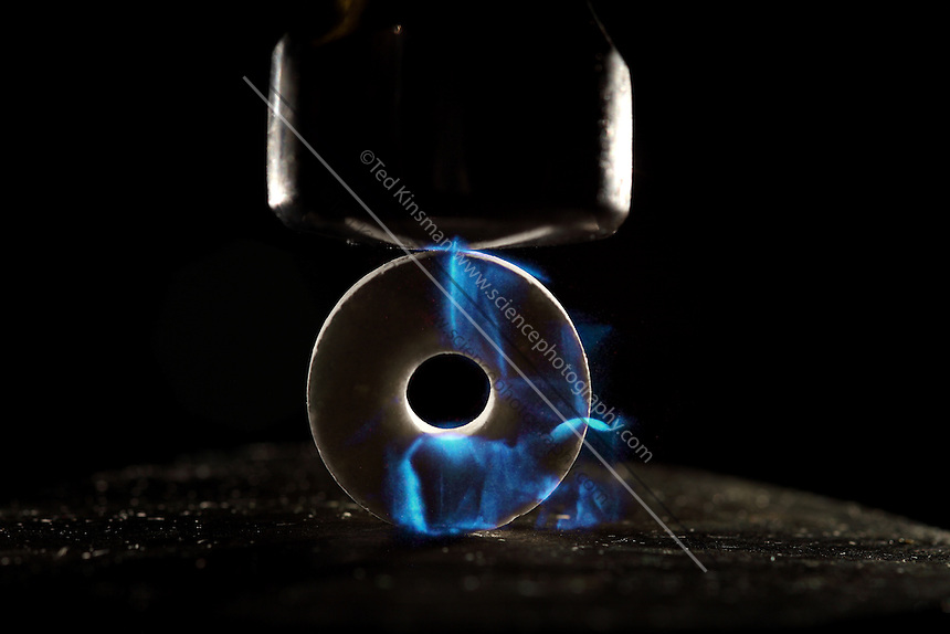 A candy is hit with a hammer to show the property of triboluminescence.  Triboluminescence is an optical phenomenon in which light is generated when asymmetrical crystalline bonds in a material are broken when that material is scratched, crushed, or rubbed.