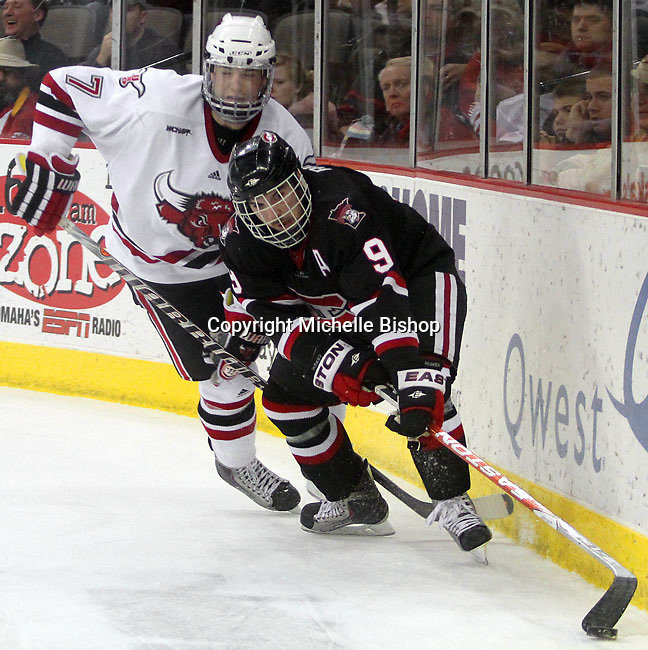 St. Cloud State's Garrett Roe tries to gain control of the puck as UNO's Michael Young approaches. UNO beat St. Cloud State 3-0 Friday night at Qwest Center Omaha.  (Photo by Michelle Bishop)
