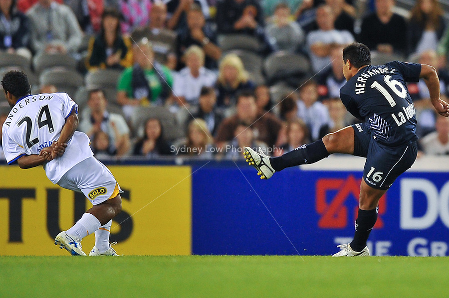 MELBOURNE, AUSTRALIA - NOVEMBER 28, 2009: Carlos Hernandez from Melbourne Victory kicks the ball as Zac Anderson takes evasive action in round 16 of the A-league match between Melbourne Victory and Gold Coast United at Etihad Stadium on November 28, 2009 in Melbourne, Australia. Photo Sydney Low www.syd-low.com