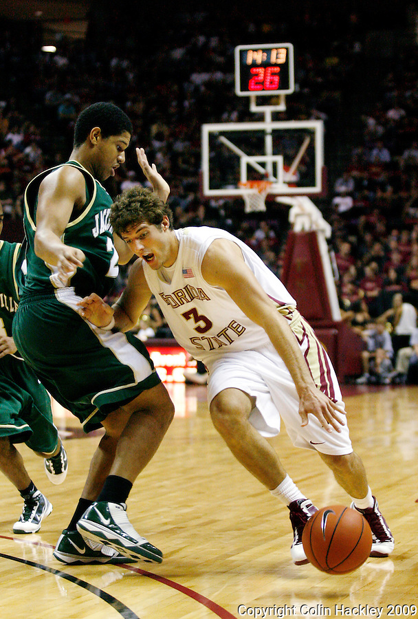 TALLAHASSEE, FL 11/16/09-FSU-JU BB09 CH25-Florida State's Luke Loucks drives by Jacksonville's Tevin Galvin during second half action Monday at the Donald L. Tucker Center in Tallahassee. The Seminoles beat the Dolphins 87-61...COLIN HACKLEY PHOTO