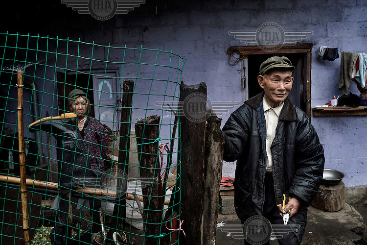 Pu Yi Na, 60, and his wife Du You Lan, 60, stand outside their home on the bank of Pula River, a tributary of the Nujiang River 2km from its confluence.