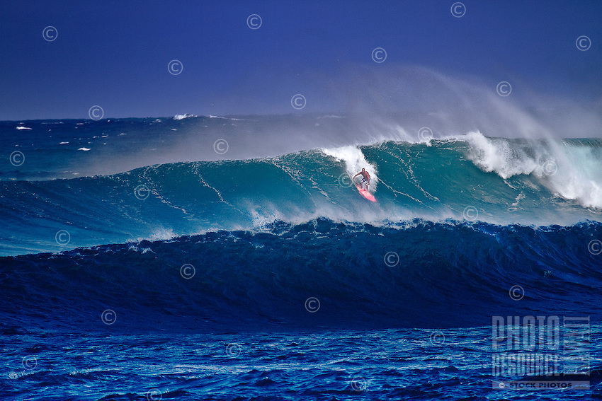Surfer riding large winter wave at Sunset Beach on North Shore of Oahu.