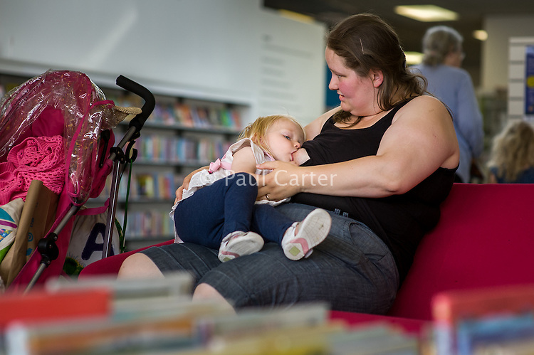A mother breastfeeding her toddler in a library.