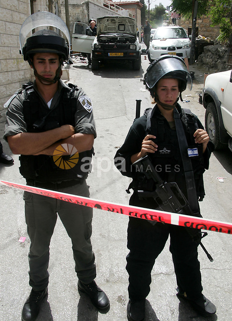 Israeli anti-riot policemen stand next to the bullet-pierced vehicle of a Palestinian man shot dead after he struck two of security officers with his car in mostly Arab east Jerusalem on June 11, 2010. Photo by Mahfouz Abu Turk