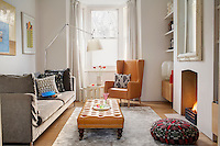 The living room is furnished with a leather Matthew Hilton wing-backed armchair, an Artemide Tolomeo floor lamp and an Antonio Citterio dove grey sofa