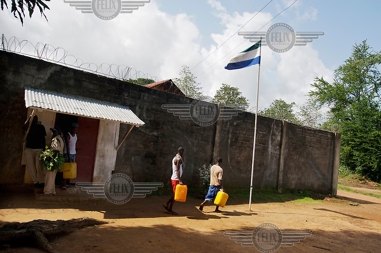 Inmates carry water containers past the Sierra Leone national flag flying outside the walls of Bo Prison.