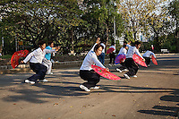 Thai women practicing dance moves with fans in park during the early morning,.Bangkok, Thailand