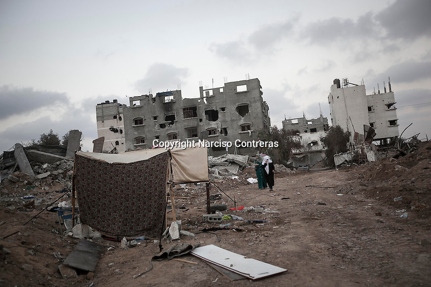 "In this Sunday, Aug. 17, 2014 photo, Palestinian women walk through what remains from her house as they look for their belongings after it was destroyed during the ""Protective Edge"" Israeli military operation in Shuyaja neighborhood in Gaza City. After a five days truce was declared on 13th August between Hamas and Israel, civilian population went back home looking for their goods in Gaza Strip. (Photo/Narciso Contreras)"