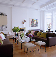 The drawing room is furnished with matching pairs of sofas, stools,and armchairs by Christian Liaigre, with an abstract painting by Christopher Wood and Man and Tortoise by Markus Luepertz