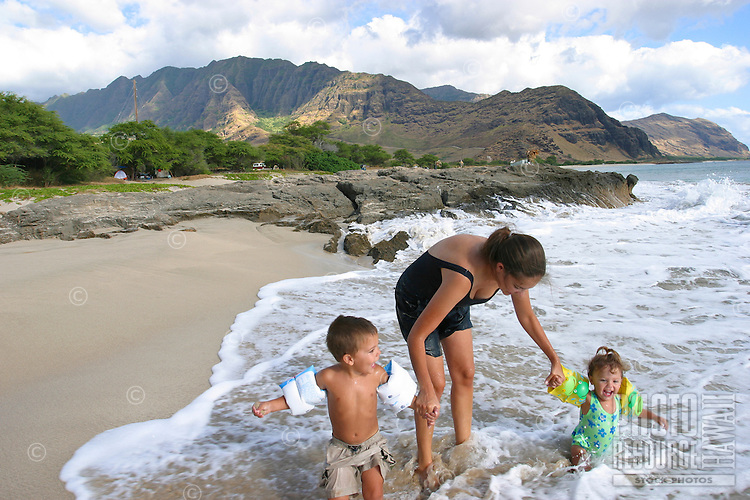 Mother playing with a boy and girl child in the surf at a beach on the west side of Oahu. Children wearing flotation devices. Mountains in the background. Wave is breaking over the family.