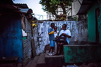 "MONROVIA, LIBERIA - FEBRUARY 19: Miatta Fanhbulleh, mother of James Nyema, 9, prepares him for school at their home, prior to the start of the fourth day of classes at the C.D.B. King Elementary School, since schools closed 6 months ago due to the Ebola outbreak, on February 19, 2015 in Monrovia, Liberia. Miatta Fanhbulleh, the mother of the boy with the pink knit mittens, James Nyema, 9, used to send him to a private school. But since she had been unemployed for months from her job as a kindergarten teacher, she had chosen to send him to C.D.B. King, a public school. Public schools are free, though parents must pay for uniforms and other supplies.<br /> She had walked her son to school in the morning with a blue plastic bag that contained his lunch and a water bottle. ""I told him when he was going, don't deal with anybody, don't drink anybody's water, don't touch anybody,"" she said, laughing, as she came to pick up her son after lunch. She had dressed him in trousers and long sleeves, which he usually wore only during the rainy season – not now, the driest and hottest time of the year. The mittens she had bought at a nearby market where they had become available during the height of the epidemic last year. Didn't she worry that her son might overheat? ""I was afraid, but what can I do?'' she said, laughing again.<br /> Daniel Berehulak for The New York Times"