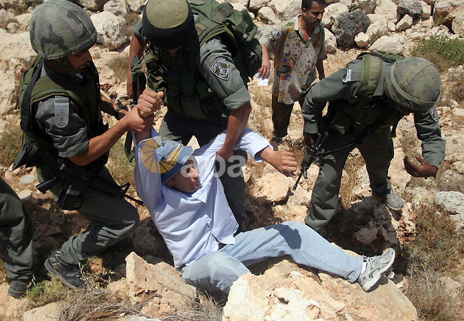 Israeli border police officers detain a Palestinian demonstrator during a protest against Israel's separation barrier in the West Bank village of Nilin, near Ramallah.