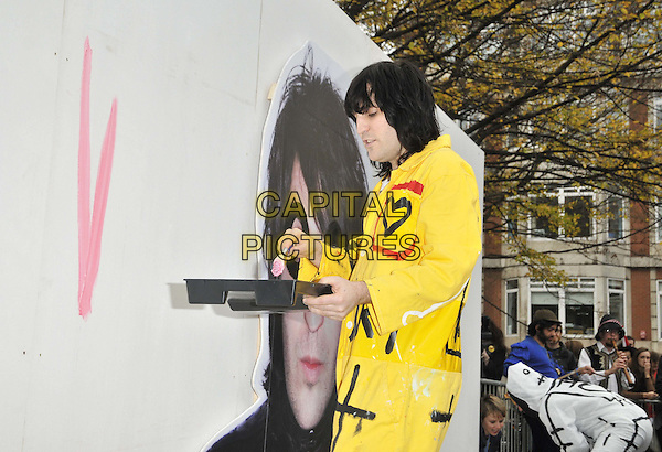 Noel Fielding.painted a billboard to promote his new book 'The Scribblings Of A Madcap Shambleton' in Golden Square, London, England, UK, 26th November 2011..photocall half length  pink paint brush painting mural  yellow boiler suit  heart graffiti .CAP/CAN.©Can Nguyen/Capital Pictures.