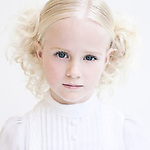 Young girl with blonde curly hair wearing white dress looking at camera