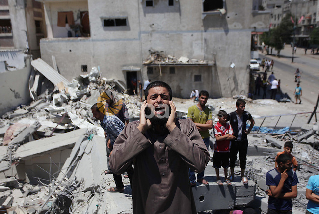 """A Palestinian muezzin """"caller of Muslims to Mosque for daily prayers"""", preforms for noon prayer as he stands on the debris of  al-Shuhada mosque, which witnesses said was hit by an Israeli air strike, in Nuseirat refugee camp in the central Gaza Strip on August 10, 2014. Israel said on Sunday it was prepared for protracted military action in Gaza and would not return to Egyptian-mediated ceasefire talks as long as Palestinians kept up cross-border rocket and mortar fire. Israeli air strikes and shelling killed three Palestinians in Gaza on Sunday, including a boy of 14 and a woman, medics said, in a third day of renewed fighting that has jeopardised international efforts to end a more-than-month-old conflict. Photo by Ashraf Amra"""