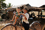 CAMBODIA  -  APRIL 3, 2005:  A girl rides a bicycle with her younger brother on the road from Kampot to Kep on April 3rd, 2005 Cambodia.  (PHOTOGRAPH BY MICHAEL NAGLE)