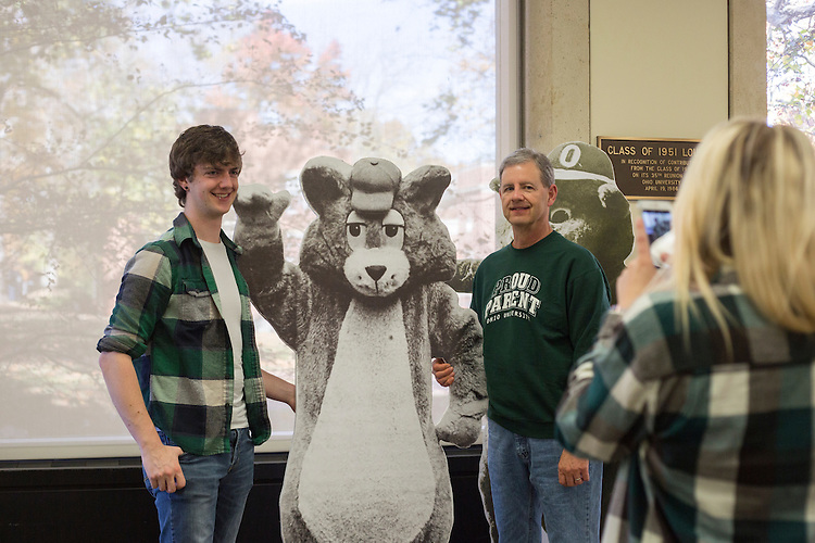 Senior Corey Bullerman, left, and his dad Bruce Bullerman, of Plains City, Ohio pose for a picture with Rufus in Alden Library during Dad's Weekend on November 5, 2016.
