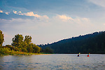 Two kayak paddlers on an evening summer float down the Bitterroot River through Missoula, Montana