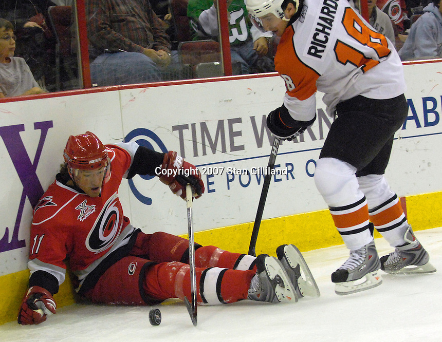 The Carolina Hurricanes' Justin Williams (11) sits on the ice after being pushed by the Philadelphia Flyers' Mike Richards (18) during their game Wednesday, Nov. 21, 2007 in Raleigh, NC. The Flyers won 6-3.