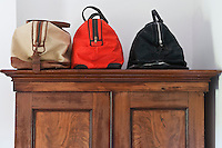 A trio of bags designed by Matt Fothergill displayed on top of the antique wardrobe in the master bedroom