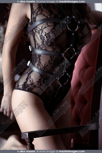 Artistic sensual closeup of a sexy woman body in black lacy underwear bodysuit with leather bondage straps tied on top