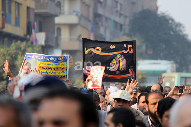 Supporters of Egypt's ousted President Mohammed Morsi hold placards and rise four fingers which has become a symbol of the Rabaah al-Adawiya mosque during a protest in Cairo, Egypt, 20 December 2013. A state prosecutor said on 18 December that deposed Egyptian president Mohammed Morsi will face trial on charges of harming national security by conspiring with the Palestinian Hamas movement. Morsi was referred to trial at a criminal court along with an unspecified number of members of his Muslim Brotherhood. Photo by Mohammed Bendari