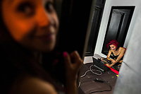 A Colombian cam model flirts with the online viewers during a video broadcast from a webcam model studio in Medellín, Colombia, 4 March 2016. With the traditional adoration of female beauty in Colombia, together with rapidly developing telecommunications technologies, the millennial generations of Colombian girls have turned the city of Medellín during the past few years into a one of the world centers of webcam modelling, a booming interractive sex industry. Thousands of young women stream everyday via websites that allow the global viewers to personally interract with a model and to pay them for sexually related acts. Although the core of the show is always based on stripping, the crucial part of a cam girl's success is communication. Cam models who have the ability of light conversation, flirting and entertaining the viewer earn thousands of dollars a month and have moved far beyond the borders of sexuality. Sharing their whole lives in a constant interaction with their online clients, they have built regular relationships in the cyberspace.