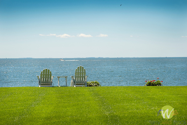 Long Island Sound, Madison, Connecticut. Two adirondack chairs overlooking water.