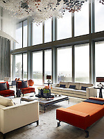 A spectacular custom lighting sculpture acts as a canopy above a social seating group shaped with Christian Liaigre's velvet sofas and spicy red chairs. The soaring double height windows flood the room with light.