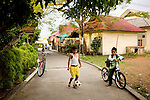 An Indonesian boy plays soccer along a narrow street in Penyenget, an island in the harbor of Tanjung Pinang, Bintan's largest city, in Indonesia, on Tuesday, April 20, 2010.