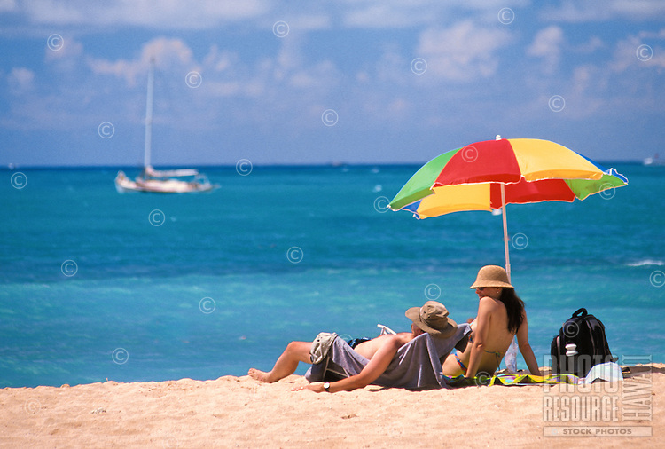 A couple relaxes in the warm sun on Waikiki Beach with a spectacular view of Hawaii's inviting blue waters.