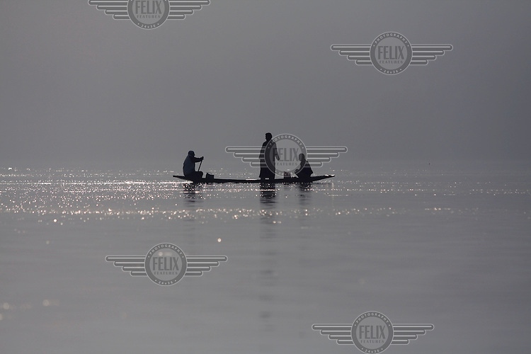 Three men in a small canoe on Dal Lake. Srinagar, Kashmir, India. © Fredrik Naumann/Felix Features