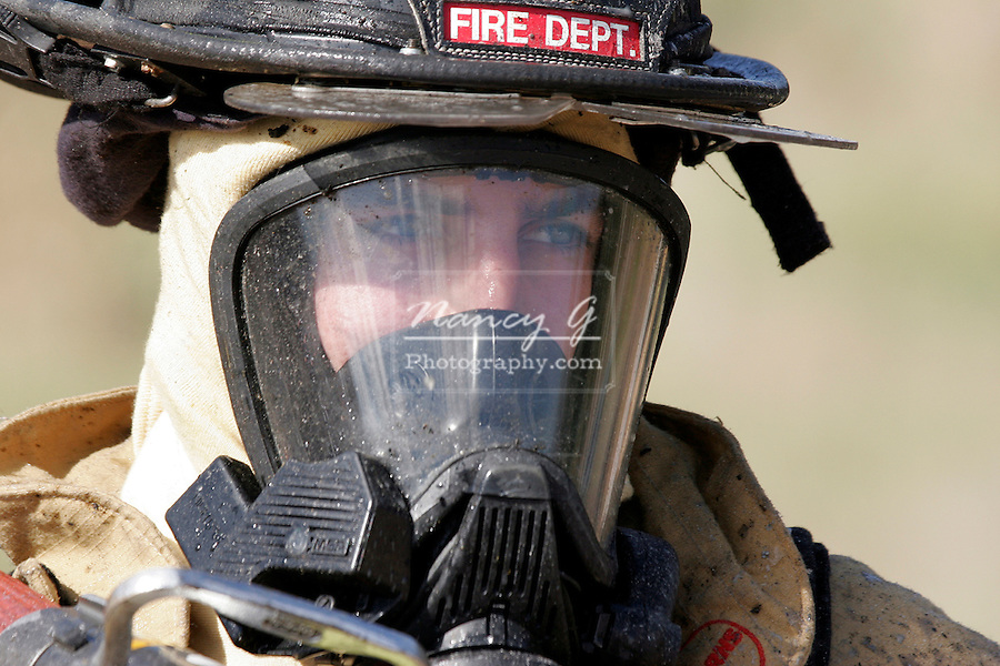 A closeup of a Fire Department firefighter looking to the right after extinguishing a structure fire