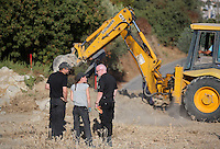 Pictured: DI Jon Cousins of South Yorkshire Police (R) watches on as a digger assists with the preliminary search at the new site in Kos, Greece. Friday 07 October 2016<br />