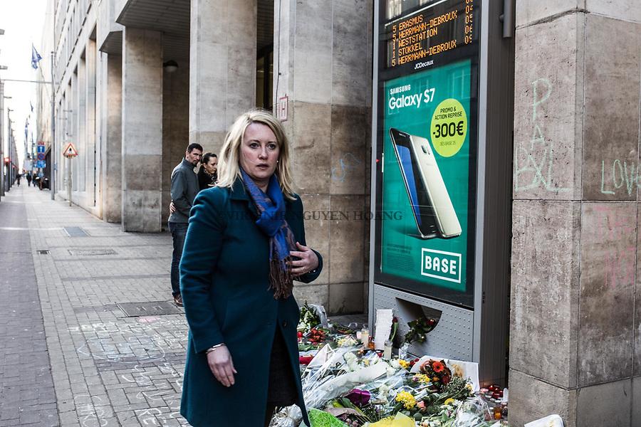 BRUXELLES,Belgique: Une jeune femme vient tout juste de déposer une bougie devant l'arrêt de métro de Maelbeek où fleurs et bougies ont été déposées en mémoire aux victimes, le 25 mars 2016.