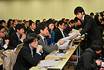 January 18, 2012, Tokyo, Japan - A staff member of the scandal-tinted Olympus distributes copies of file to the media before the start of a news conference by its President Shuichi Takayama in Tokyo on Wednesday, January 18, 2012. Takayama told the news conference that the current leadership, including Takayama himself, would remain in office for another three months as the camera and medical equipment maker prepared for an extraordinary shareholders' meeting in the latter half of April...Olympus set up the news conference a day after the company-appointed independent panel cleared auditing firms from responsibility for the company's accounting scandal but found five current and former individual auditors culpable, which means Olympus won't take legal action against its outside accounting firms for failing to uncover a 13-year effort to hide $1.5 billion in investment losses. (Photo by Natsuki Sakai/AFLO) AYF -mis-.