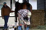 A farrier shoeing a horse in the barn at Oaklawn Park 1-11-13. (Justin Manning/Eclipse Sportswire)