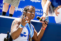 Second place finisher Minda is interviewed during the Awards Ceremony after the Aquaphor New York City Triathlon in New York on July 8, 2012.