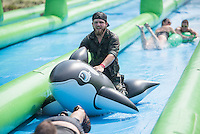 NWA Democrat-Gazette/J.T. WAMPLER Dakota Guenther of Sprindale rides an inflatable orca down a 1,000 foot long water slide on Dickson St. in Fayetteville Sunday August 30, 2015. The water slide was brought to Fayetteville by Slide the City, a company based in Salt Lake City. Part of the event's proceeds will benefit Soldier On Service Dogs, a nonprofit organization that raises, trains and gives away service dogs to veterans who have post-traumatic stress disorder or traumatic brain injuries. For more photos of the event go to http://nwamedia.photoshelter.com/