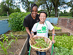 4-H ambassador Caleb Kinzinger, 16, from Freeburg, Ill and Jackie Joyner Kersee with vegetables for a salad at the urban garden on Thursday, May 30, 2019 in East St. Louis, Ill. (Tim Vizer/AP Images for National 4-H Council)