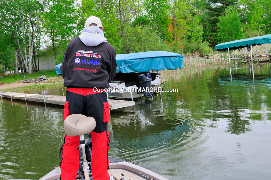 00416-028.14 Fishing:  Angler in boat is skipping a jig and plastic combo under a dock.  Bass, largemouth, smallmouth.3