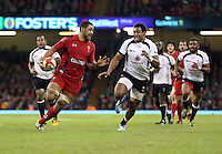 Pictured: Taulupe Faletau (L) against Waisea Nayacalevu of Fiji (R) on his run for a try for Wales. Saturday 15 November 2014<br />