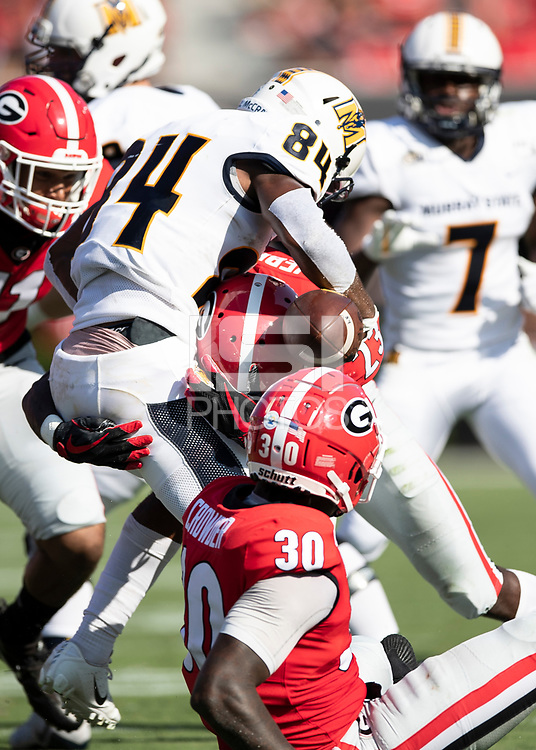 ATHENS, GA - SEPTEMBER 7: Mark Webb #23 hits the ball causing Jared McCray #84 to fumble resulting in a Georgia touchdown by JR Reid during a game between Murray State Racers and University of Georgia Bulldogs at Sanford Stadium on September 7, 2019 in Athens, Georgia.
