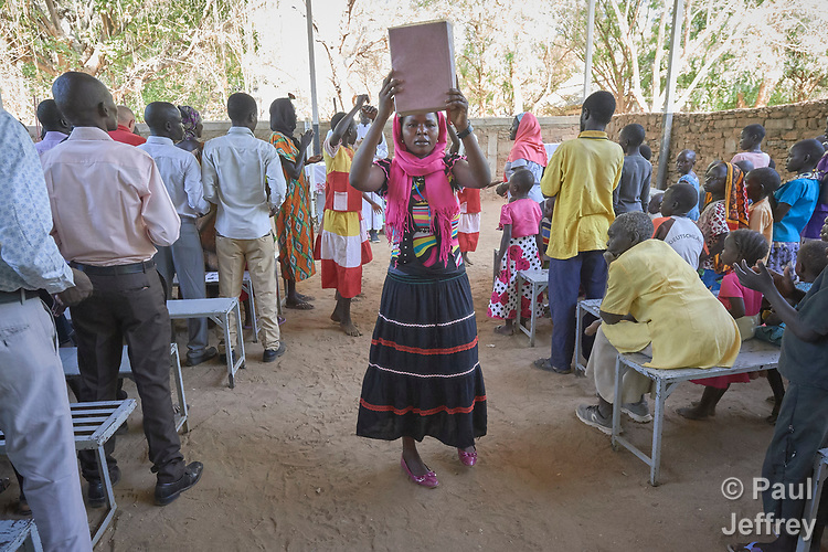 A woman carries the Bible into a Catholic Mass in Gidel, a village in the Nuba Mountains of Sudan. The area is controlled by the Sudan People's Liberation Movement-North, and frequently attacked by the military of Sudan.