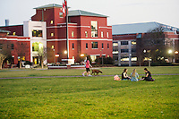 Drill Field at dusk, with <br /> students sitting on grass, enjoying mild temperatures: Delaney Gillespie (maroon),  Mary Anne Goolsby (grey), Giulia Hintz (black).<br />  (photo by Megan Bean / &copy; Mississippi State University)