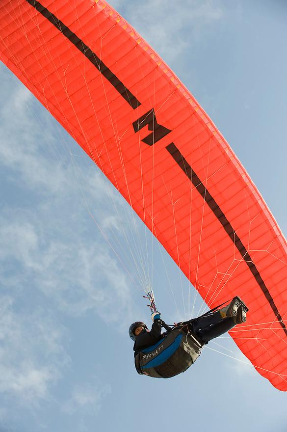 Nederland, Rotterdam, 11 april 2008.Paragliders zeilen op een aangename bries boven het strand en de duinen van de maasvlakte. Paragliders hangen in een stoeltje onder een soort grote vlieger en kunnen zo lang in dus lucht blijven. Een duin is voldoende om te kunnen starten....Foto (c) Michiel Wijnbergh