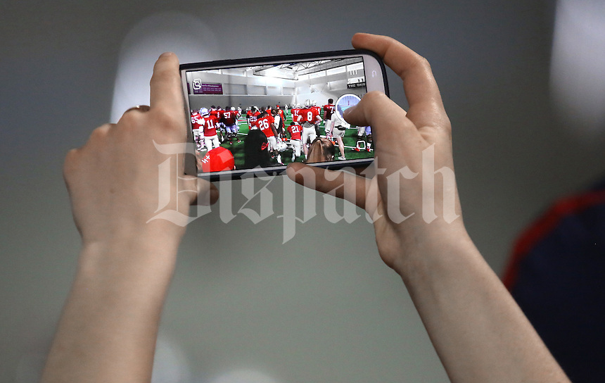Students raise their phones to take photos of the Buckeye Football team practicing at the Woody Hayes Athletic Center on April 11, 2015. Students were invited to the facility for the fourth annual Student Appreciation Practice .  (Chris Russell/Dispatch Photo)